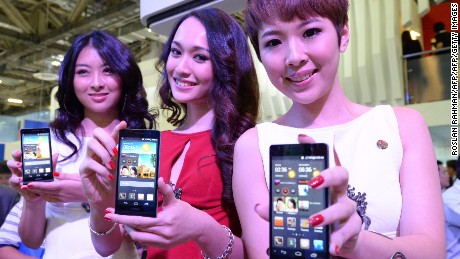 Promoters display Huawei's Ascend P6 phone, billed as the world's thinnest smartphone, at the CommunicAsia telecom and broadcast event in Singapore on June 19, 2013 just hours after its global launch in London. Chinese telecom giant Huawei on June 19 vowed to catch up with its more popular rivals Apple and Samsung after unveiling its newest phone for the first time in Asia.   AFP PHOTO/Roslan Rahman        (Photo credit should read ROSLAN RAHMAN/AFP/Getty Images)