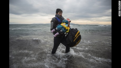 A man carries a child as they try to reach a shore 