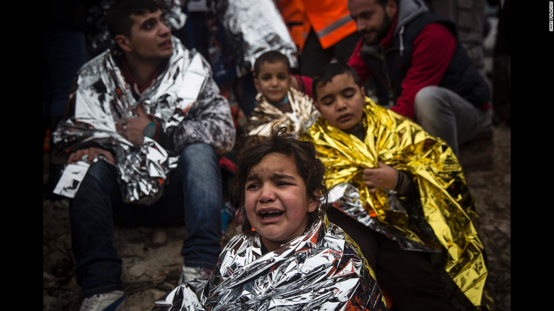 Refugees wrap themselves with thermal blankets as they sit on a beach shortly arriving on Lesbos on January 3.