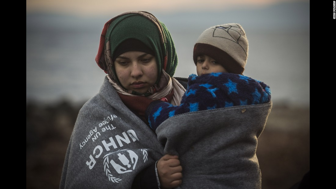 A woman holds a child on the beach after arriving in Lesbos on January 3.