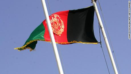 "Lashkar Gah, AFGHANISTAN:  An American flag is lowered beside an Afghan flag at the ""Transition of Authority"" ceremony at the Provincial Reconstruction Team (PRT) base at Lashkar Gah in Helmand, 1 May 2006, as US forces officially hand over the Helmand base to British control.  Britain's deployment of 3,300 troops -- tripling the 1,100 already stationed there as part of a multi-national operation working on counter-narcotics and reconstruction -- will be part of the NATO-led International Security Assistance Force.    AFP PHOTO / JOHN D MCHUGH  (Photo credit should read JOHN D MCHUGH/AFP/Getty Images)"