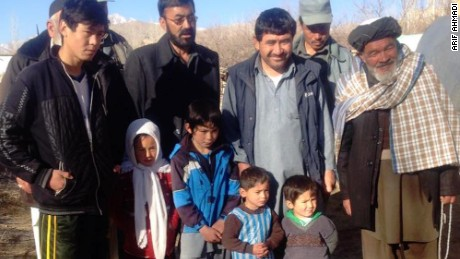 Murtaza poses with local villagers, including his proud father Arif, in the blue vest, third from right.