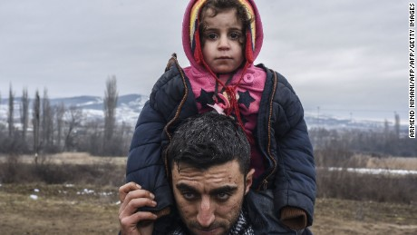 A man carries a child as migrants and refugees wait in line for security check after crossing the Macedonian border into Serbia, near the village of Miratovac, on January 26, 2016. More than 1 million people from countries like Syria, Iraq or Afghanistan entered Europe last year in what has been called the biggest migration to the continent since World War II.   / AFP / ARMEND NIMANI        (Photo credit should read ARMEND NIMANI/AFP/Getty Images)