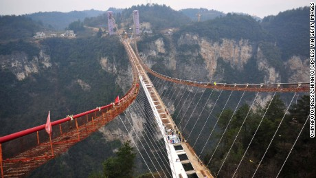 Workers install a piece of glass on a suspension bridge, approximately 300 meters above ground at the Grand Canyon of Zhangjiajie on January 27, 2016. The glass-bottomed bridge, 430 meters in length and 6 meters in width, is expected to open in May this year.