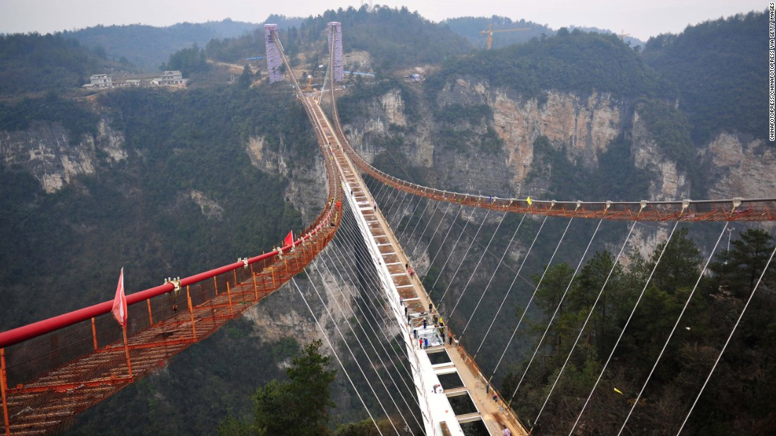 Workers recently began installing glass on what will be the world's longest glass-bottom bridge. Due to open in May, it's 430 meters long, six meters wide and hovers over a 300-meter vertical drop in China's Hunan province.