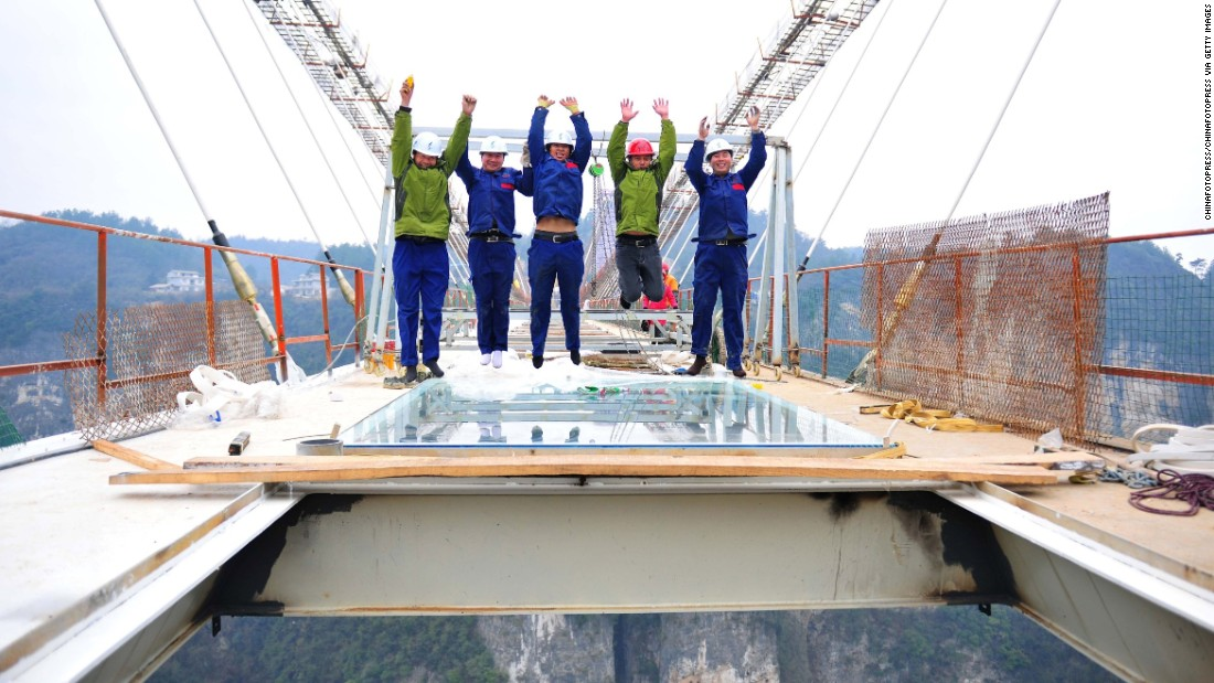 Workers installing the bridge's glass demonstrate just how confident they are in their work by leaping into the air for a picture on January 27.
