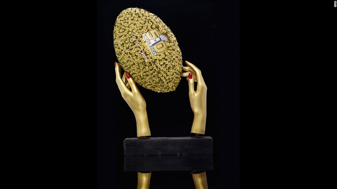 The National Football League has teamed up with 50 designers from the Council of Fashion Designers of America on a series of wildly embellished footballs. This <strong>Betsey Johnson</strong> piece features gold rosettes. Take a look at the other wild designs...