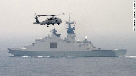 A US-made S-70C helicopter files over a French-made Lafayette frigate during a drill at sea near the naval port in Kaohsiung in southern Taiwan on January 27, 2016.  The Taiwanese military launched a series of mini military drills the last two days to display their determination to defend itself against China amid concerns if tensions would be stoked across the Taiwan Strait following the island's recent presidential vote.