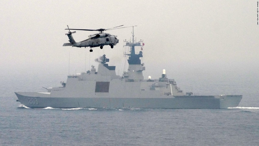 A U.S.-made S-70C helicopter files over a French-made La Fayette-class frigate during a drill off the naval port in Kaohsiung on January 27.