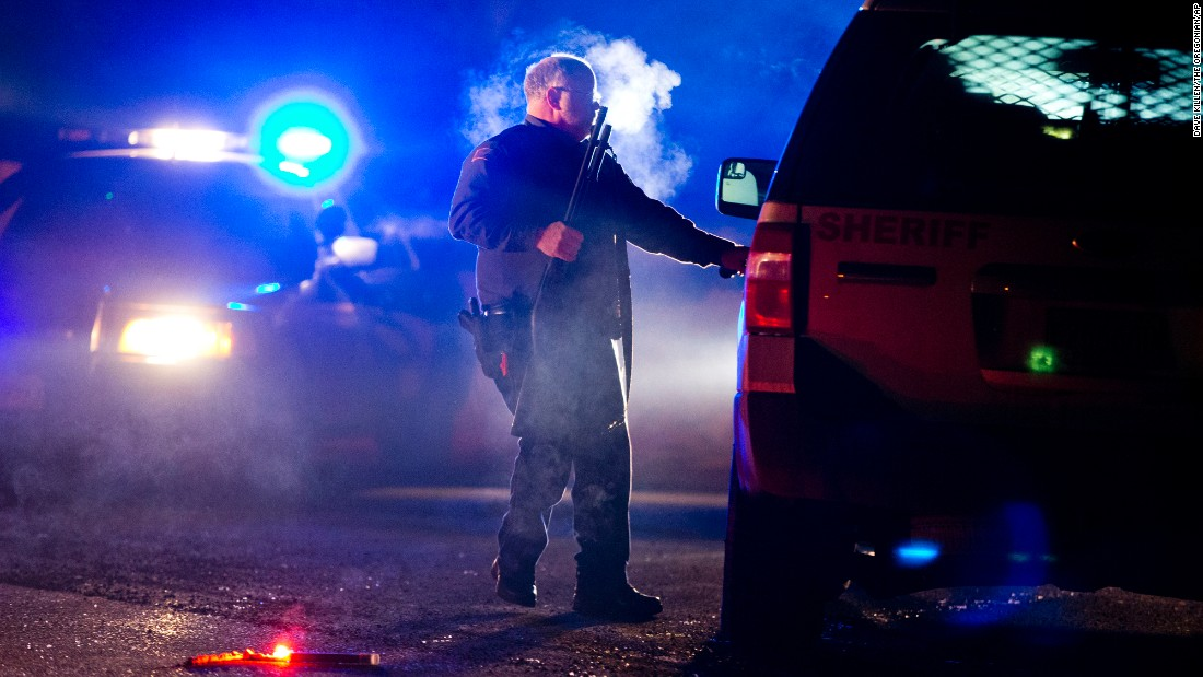 "An Oregon state police officer stands by a vehicle as police officers block Highway 395 in Seneca, Oregon, on Tuesday, January 26. The road was blocked to <a href=""http://www.cnn.com/2016/01/27/us/oregon-siege-traffic-stop/"" target=""_blank"">arrest leaders of an armed group</a> that has been occupying a national wildlife refuge since January 2."