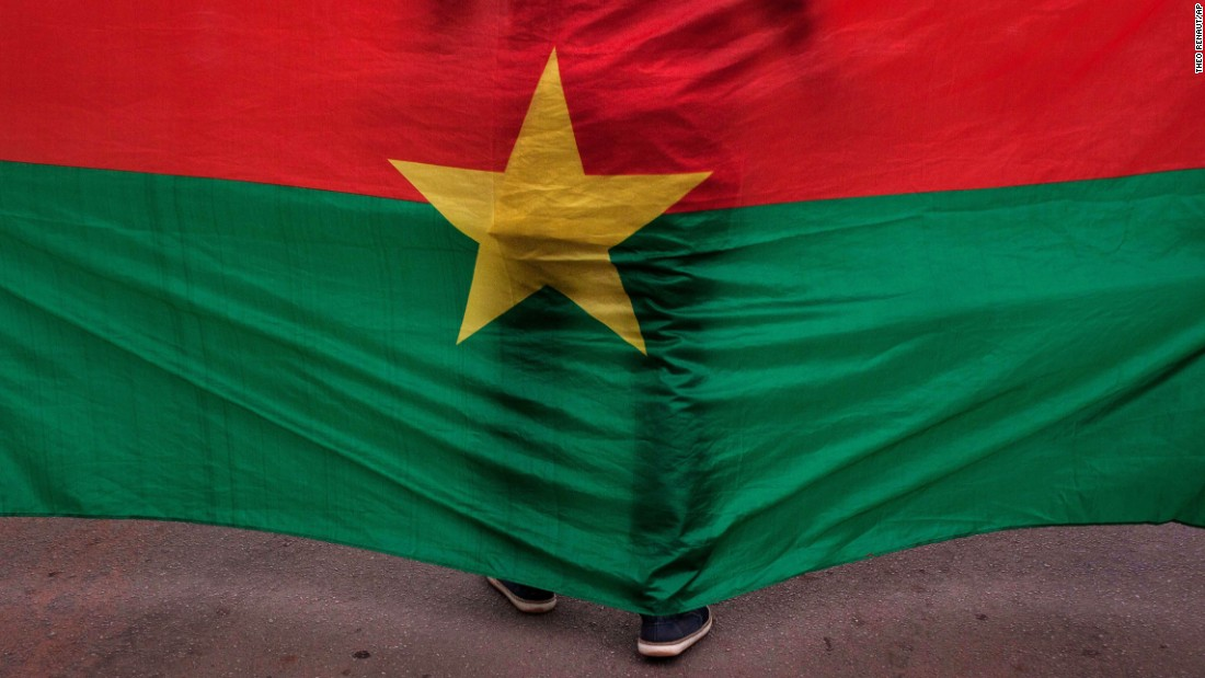"A man in Ouagaougou, Burkina Faso, stands in front of the country's flag during a memorial ceremony held Saturday, January 23, for victims of <a href=""http://www.cnn.com/2016/01/16/africa/burkina-faso-hotel-terrorist-attack/"" target=""_blank"">a recent hotel attack.</a> An al Qaeda-linked terrorist group claimed responsibility for the assault at Splendid Hotel."