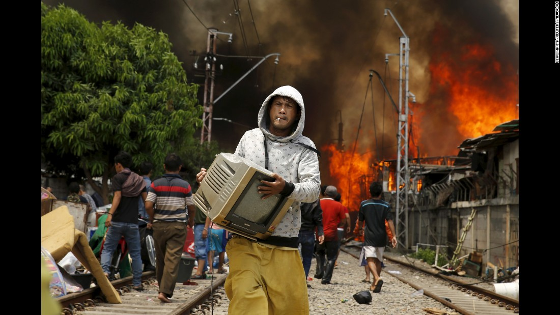A man carries a television away from a fire in North Jakarta, Indonesia, on Tuesday, January 26. According to local media, the fire destroyed approximately 100 wooden dwellings built along a busy railway line.