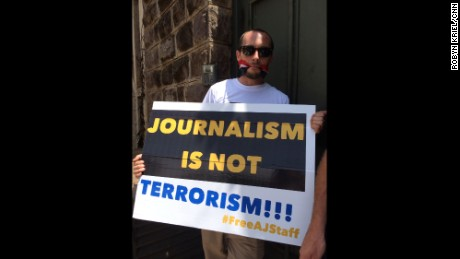In this February 2014 picture taken in Nairobi, Phil Moore holds a sign advocating for the release of Al Jazeera journalists held until recently in Egypt.