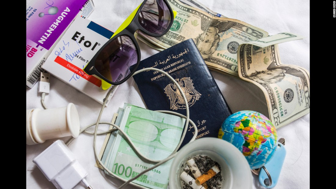 A close-up of Somar's Syrian passport, along with money and a few other objects.