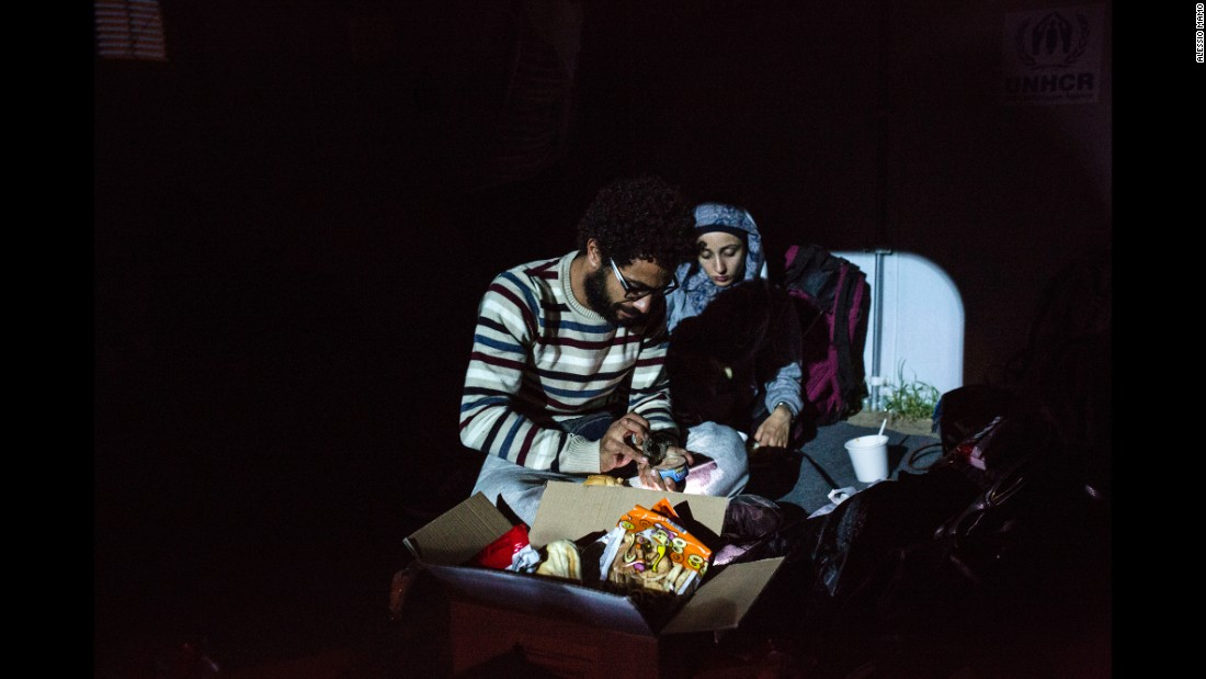 Somar and his sister Salsabil open a box of canned food inside a U.N. camp.
