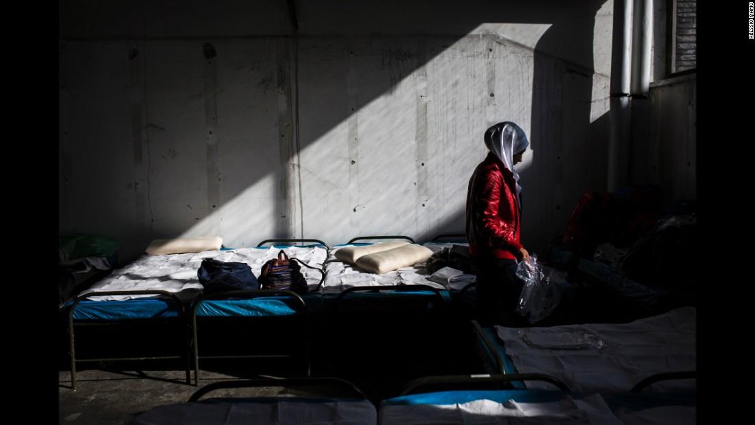 Salsabil fixes beds inside a transit refugee camp.