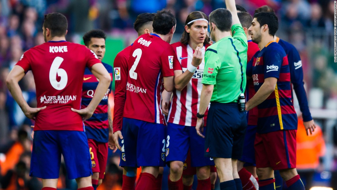 Referee Alberto Undiano Mallenco shows a red card to Filipe Luis after fouling Lionel Messi.