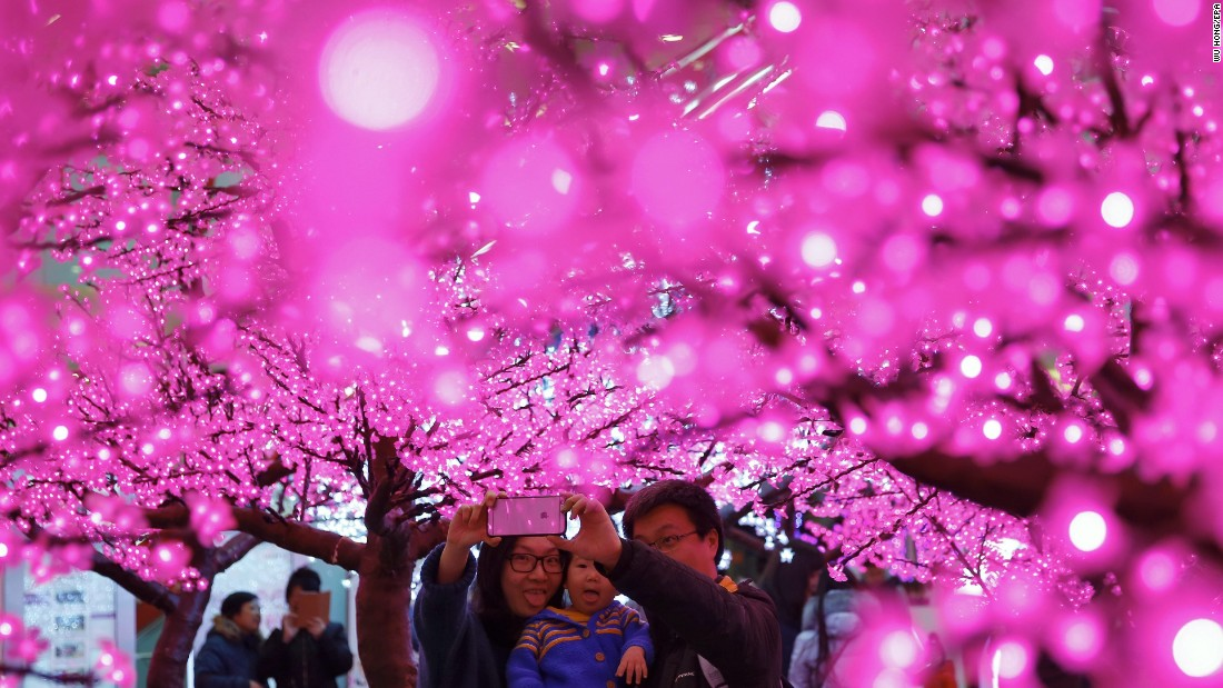 A family takes a selfie in front of artificial trees decorated with lights in Beijing on January 30.
