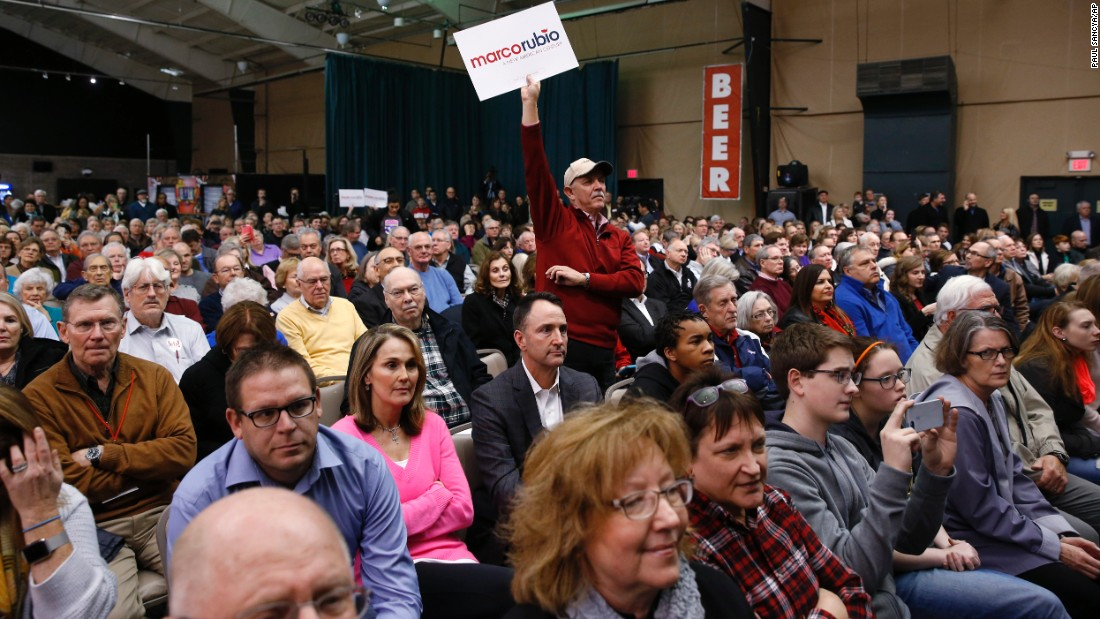 A Rubio supporter holds a sign at a caucus site in Clive, Iowa.