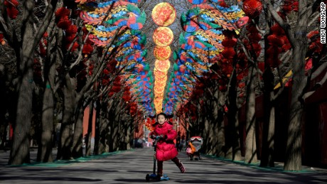 A girl rides on a child's scooter under decorations for a temple fair ahead of the Chinese Lunar New Year at Ditan Park in Beijing, China on Tuesday, February 2.