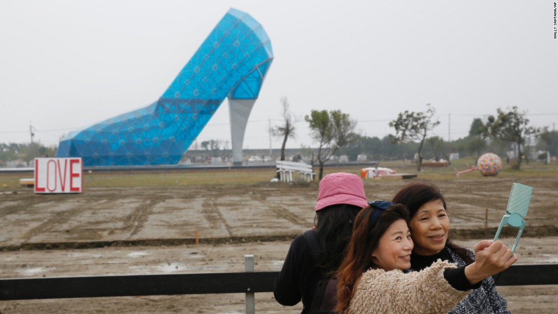 People in Chiayi, Taiwan, take a selfie in front of a glass structure shaped like a high-heeled shoe on Thursday, January 28. The shoe will be a wedding hall when it opens later this month.
