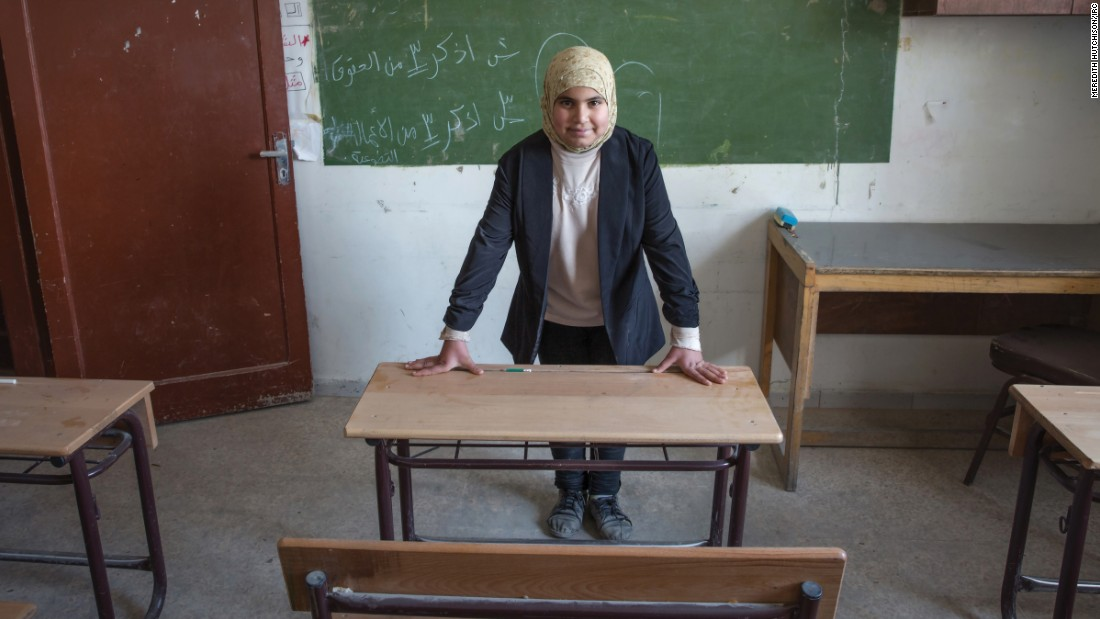 """In this image, it is the early morning, and I am waiting in my classroom for my students to arrive. I teach younger children to read and write Arabic. I am strict, but I go out of my way to gently help those students who are having difficulties."""