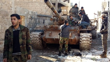 Syrian government forces chat near a tank three kilometers from the Shiite villages of Nubul and Zahraa.