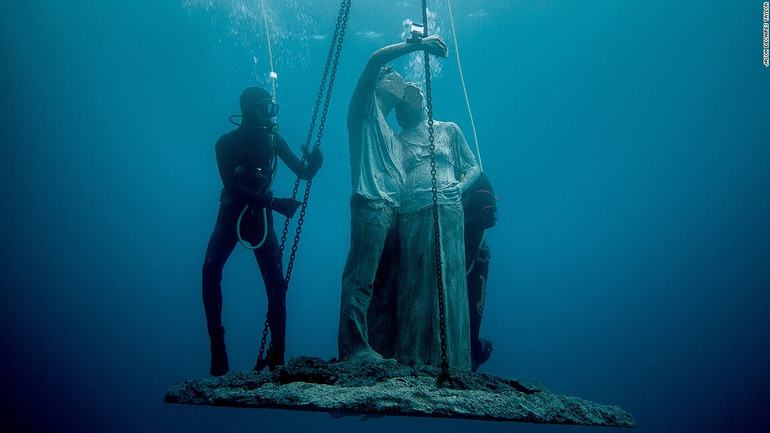 "A sculpture named ""Content,"" featuring a faceless couple taking a selfie, is lowered into the sea."