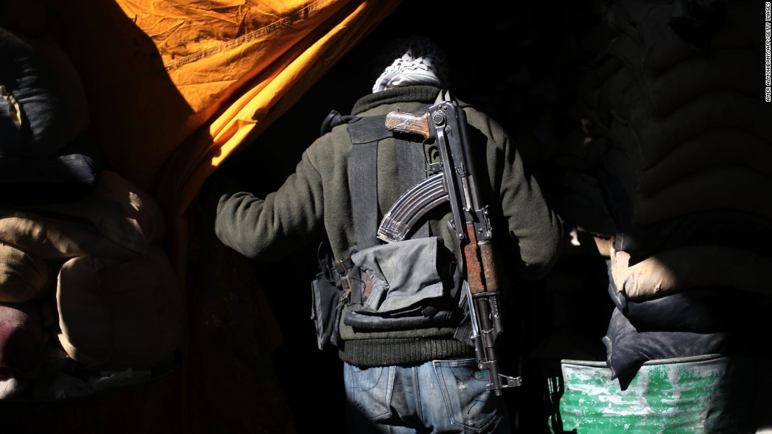 A Syrian rebel fighter walks past sandbags in Arbin, Syria, on Friday, January 29.
