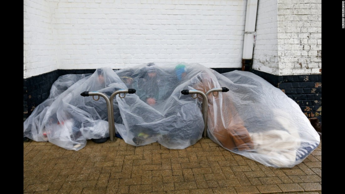 Refugees protect themselves from the rain under a plastic cover in Zeebrugge, Belgium, on Wednesday, February 3.