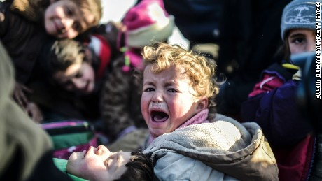 A Syrian child cries as Syrians flee the northern embattled city of Aleppo wait.