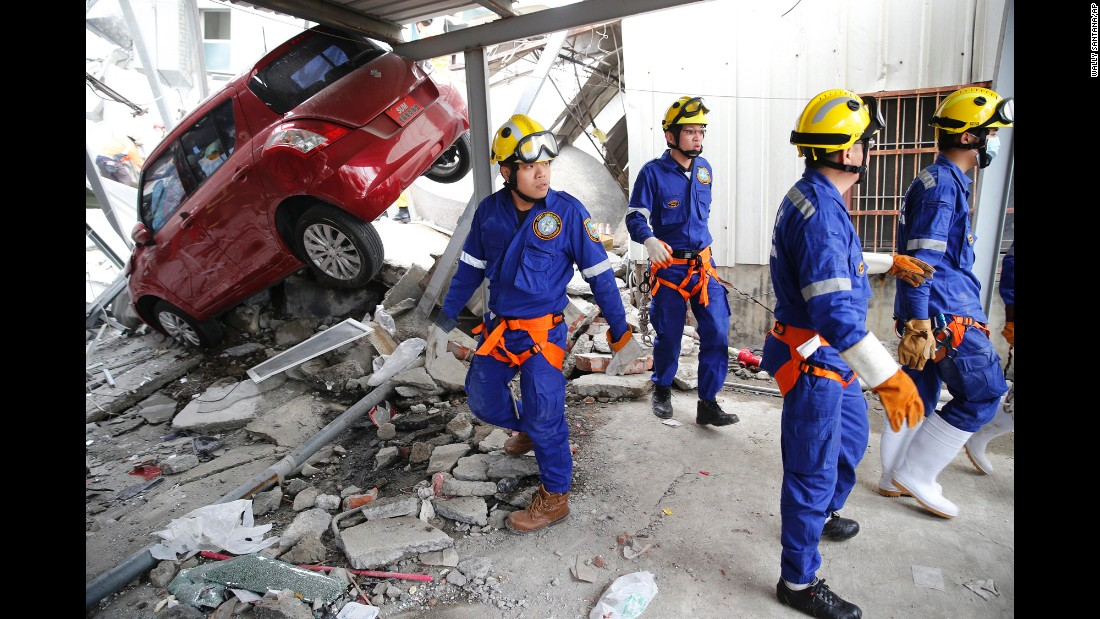 Rescue workers search a collapsed building in Tainan.