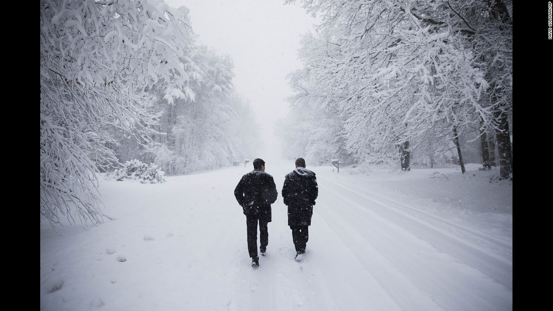 Dave Chiokadze, left, and James Radcliffe, volunteers for Republican presidential candidate Donald Trump, walk through the snow knocking on doors in search of Trump supporters in Londonderry, New Hampshire, on February 5.