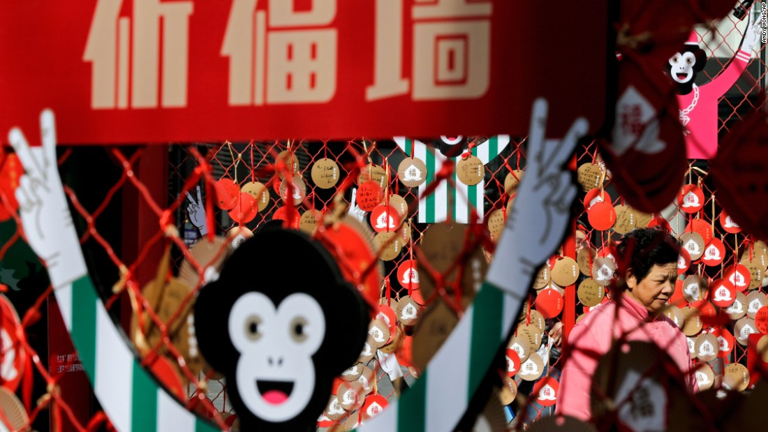 A woman in Beijing walks past New Year wish cards on Thursday, February 4.