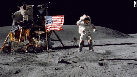 Astronaut John Young leaps from the surface of the moon as he salutes the U.S. flag.