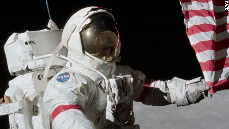 """Mission commander Gene Cernan holds the corner of the American flag during the first Apollo 17 moonwalk. Cernan was the last man on the moon. He had these parting words as he left: """"We leave as we came and, God willing, as we shall return, with peace, and hope for all mankind."""""""