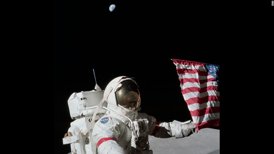 "Cernan holds a corner of the American flag during the first Apollo 17 moonwalk. Cernan, the last man on the moon, had these parting words as he left: ""We leave as we came and, God willing, as we shall return -- with peace, and hope for all mankind."""