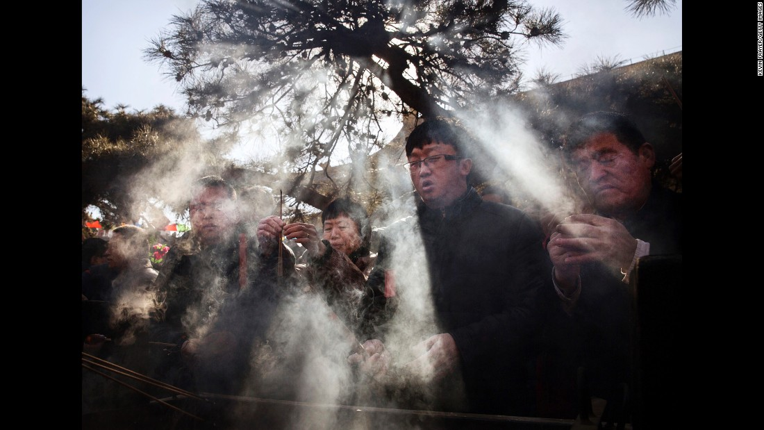 People light incense and pray at the Yonghegong Lama Temple in Beijing on February 8.