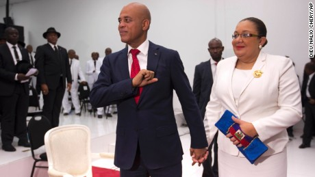 Michel Martelly, Haiti's outgoing President, stands with his wife, Sophia, before they leave parliament chambers in Port-au-Prince on Sunday.
