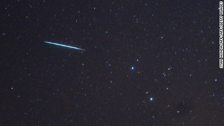 """A meteor (L) from the Geminids meteor shower enters the Earth's atmosphere past the stars Castor and Pollux (two bright stars, R) on December 12, 2009 above Southold, New York. This meteor shower gets the name """"Geminids"""" because it appears to radiate from the constellation Gemini. Geminids are pieces of debris from an asteroid called 3200 Phaethon. Earth runs into a stream of debris from the object every year in mid-December, causing the meteors. The peak of the shower is expected the night of December 13-14 at about 0500 GMT on December 14.  AFP PHOTO/Stan Honda        (Photo credit should read STAN HONDA/AFP/Getty Images)"""