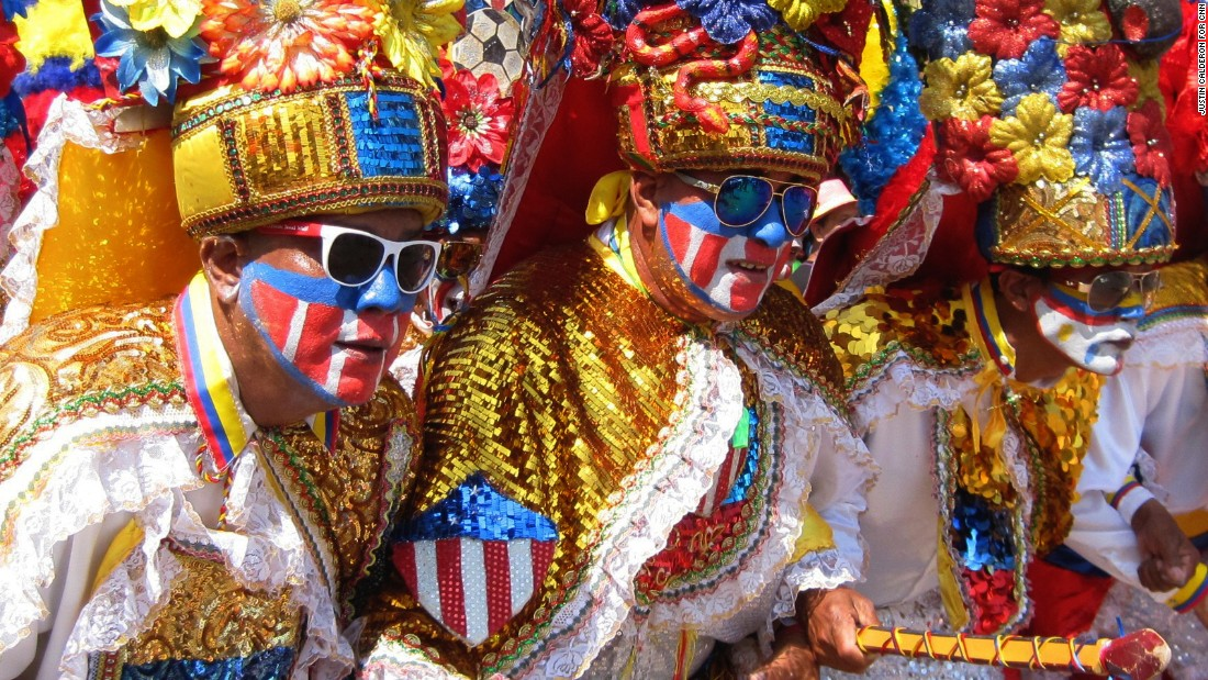 Men painted in Colombian colors dance congo, a traditional warrior's dance from Africa.