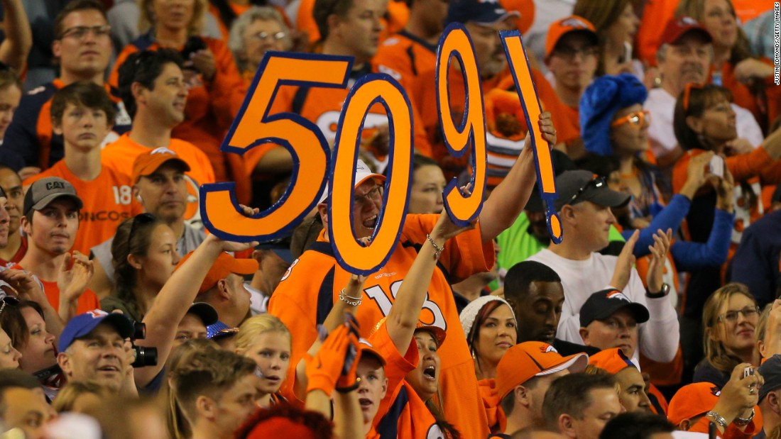 Denver fans celebrate in 2014 after Manning threw his 509th career touchdown pass, breaking the NFL record held by Brett Favre.