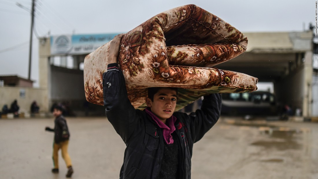 A young refugee carrying belongings arrives at the Turkish border on February 6.