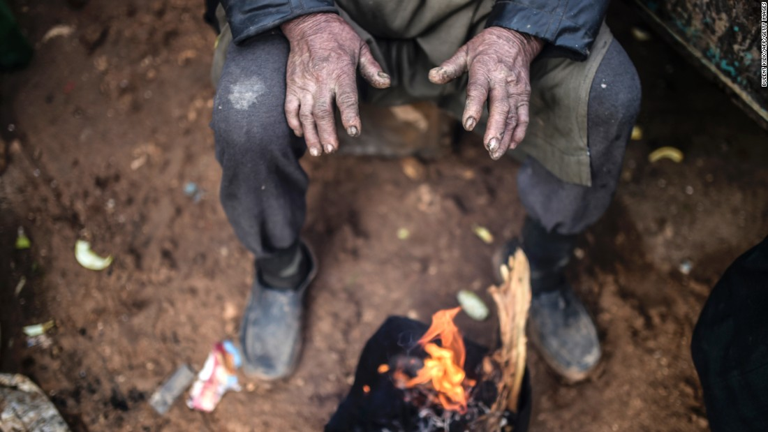 A refugee warms himself at a bonfire near the Turkish border on February 6.