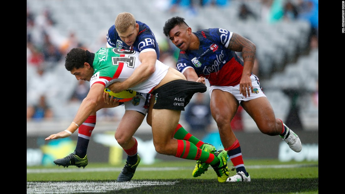 Kyle Turner, a rugby player with the South Sydney Rabbitohs, is tackled by two Sydney Roosters during an Auckland Nines match in Auckland, New Zealand, on Saturday, February 6.