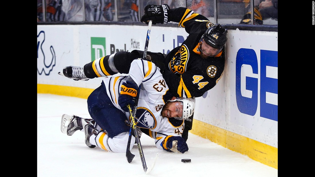 Boston's Dennis Seidenberg falls on Buffalo's Daniel Catenacci during an NHL game in Boston on Saturday, February 6.