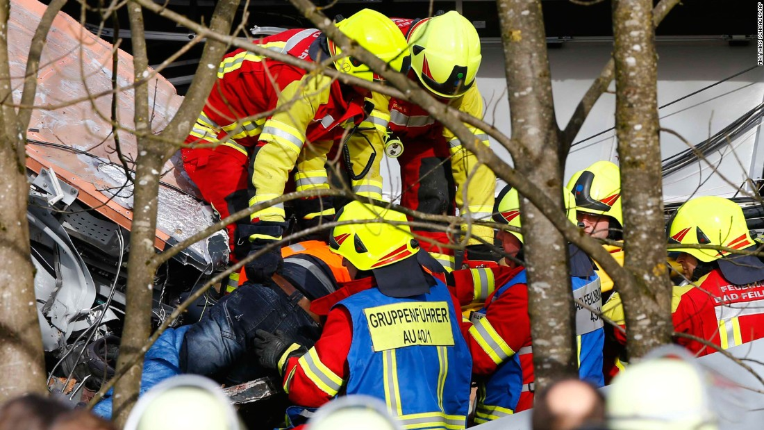 Rescue workers salvage a body at the site of the crash.
