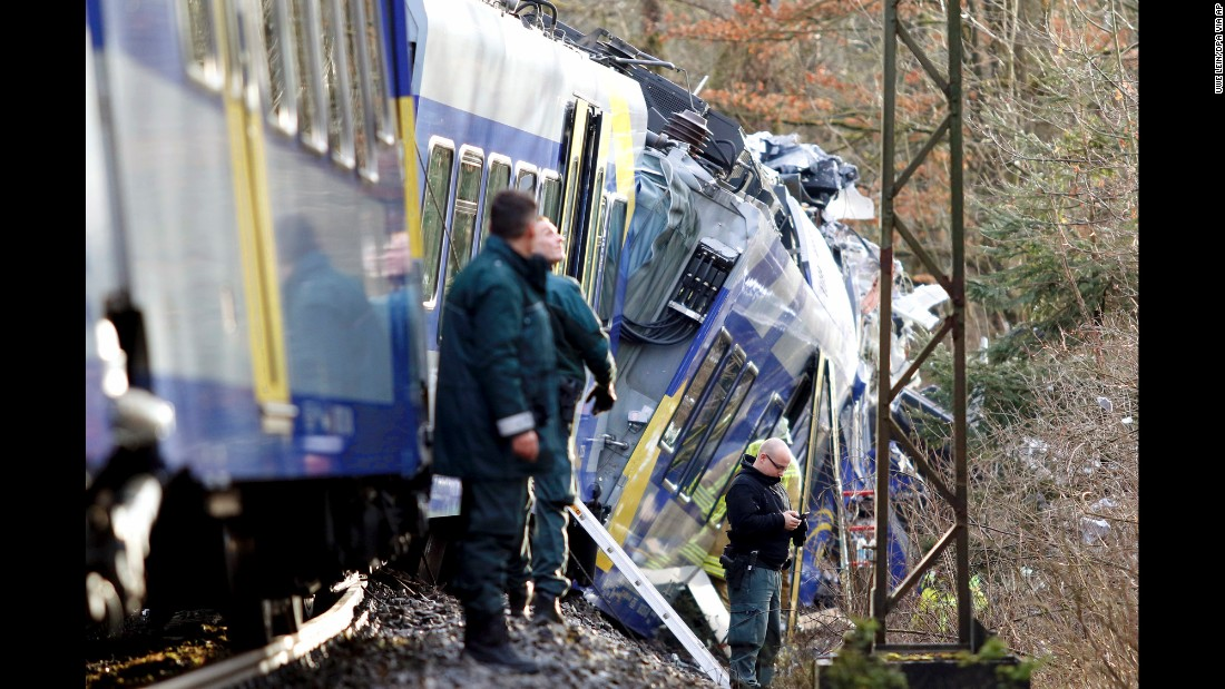 Police stand beside the trains as rescue personnel search the wreckage.