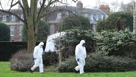Forensics officers study the scene near where a man set himself on fire Tuesday outside Kensington Palace.