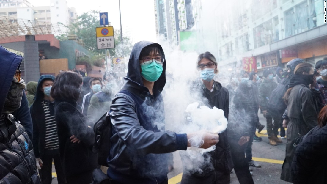 A protester holds a smoking object before throwing it at riot police on February 9.